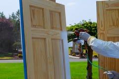 Close-up van spuitpistool met verf schilderende Meester die houten deuren schilderen royalty-vrije stock fotografie