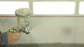 Close-up van spuitpistoolverf terwijl het werken bij het benzinestation stock videobeelden