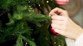 Close-up van stuk speelgoed van de hand het hangende Kerstmis van de vrouw Het verfraaien van Kerstmisboom Nieuwjaar en Kerstmisv stock videobeelden