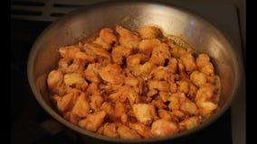 Close-up van stukken van het kruidige met kerrie gekruide kip braden in olie in een pan stock footage
