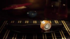 Close-up van sushibroodje op plaat Het eenzame sushibroodje met zalm en kaas is op zwarte plaat, die indient zwarte neemt stock videobeelden