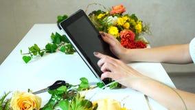 Close-up van tablet waarop de handen van het bloemistmeisje ` s vingers onder bloemenregelingen op bureau in bureau in dag leiden stock video