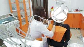 Close-up van tandarts die jonge vrouwen` s tanden onderzoeken stock video