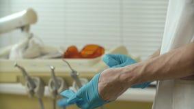 Close-up van tandarts het zetten op blauwe gesteriliseerde latexhandschoen stock videobeelden