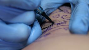 Close-up van tatoegeringskunstenaar die een tatoegering in studio doen stock footage