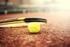 Close-up van tennisbal en racket op kleihof Stock Foto