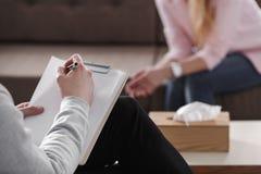 Close-up van therapeuthand het schrijven nota's tijdens het adviseren ses royalty-vrije stock foto
