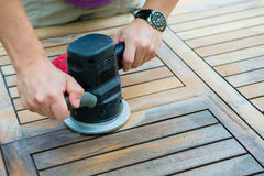 Close-up van timmermans` s handen die met elektrische schuurmachine werken stock fotografie