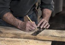 Close-up van timmermans` s ruwe ruwe handen die een potlood en een oud vierkant gebruiken om een lijn op houten te snijden raad t stock afbeelding