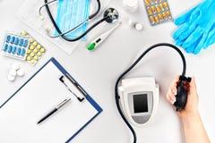 Close-up van tonometer door patiëntenwapen die tijdens bloeddruk bij medisch overleg meten stock fotografie