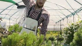 Close-up van tuinhulpmiddelen Tuinman die naar de serre, het water geven installaties van een groene trechter gaan Tuincentrum stock video