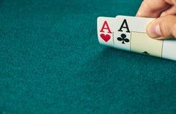 close-up van twee die azen in ??n hand op de groene spelmat worden gehouden op de rechterkant van het beeld om ruimte te verlaten royalty-vrije stock afbeelding