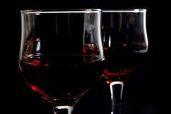 Close-up van Twee die Wijnglazen met Rode Wijn op Zwarte worden gevuld Stock Afbeeldingen