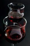Close-up van Twee die Wijnglazen met Rode Wijn op Zwarte worden gevuld Royalty-vrije Stock Fotografie