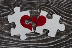 Close-up van twee gescheiden stukken van een raadsel die samen een hart op een rustieke houten oppervlakte vormen royalty-vrije stock foto's