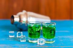 Close-up van twee groene schoten van de alsemalcohol met stock afbeeldingen