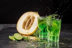 Close-up van twee heldere dragon bespattende cocktails op een zwarte achtergrond Dranken met dragon, zoete besnoeiingsmeloen, ijs Stock Foto's