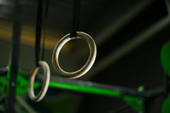 Close-up van twee houten nog ringen, regelmatige ringen die, gesteund door een riem op een donkere vage achtergrond vrij hangen Stock Afbeelding