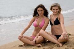 Close-up van twee jonge vrouwen die op het strand glimlachen royalty-vrije stock afbeelding