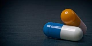 Close-up van twee medische capsules op een leiplaat Royalty-vrije Stock Afbeelding
