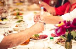 Close-up van twee mensen die glazen met wodka clinking bij restaurant Stock Afbeeldingen