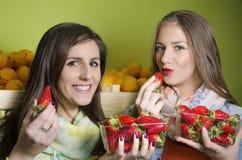 Close-up van twee natuurlijke, mooie meisjes die aardbeien eten Royalty-vrije Stock Afbeelding