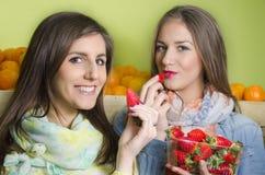 Close-up van twee natuurlijke, mooie meisjes die aardbeien eten royalty-vrije stock fotografie