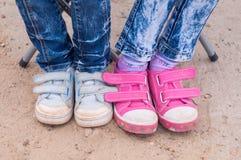 Close-up van twee paren voeten van kinderen gekleed in jeans en tennisschoenen Stock Fotografie