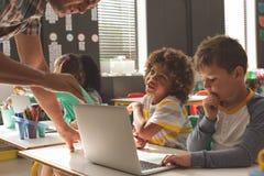 Close-up van twee schooljongens het luisteren een leraar die hen verklaren hoe te om laptop te gebruiken stock afbeelding