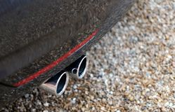 Close-up van tweelinguitlaatpijpen gezien uitzendend dampen van een Duitser gemaakt tot auto stock foto