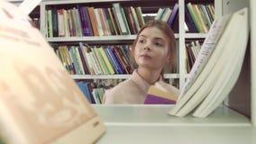 Close-up van universiteitsmeisjes die boeken in bibliotheek kiezen stock footage