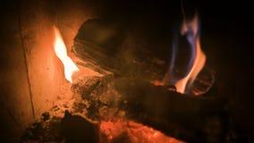 Close-up van vaag het branden van brandhout met steenkolen in een modern huisfornuis achter een vuurvast glas bij nacht Het bekij stock videobeelden