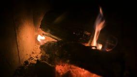 Close-up van vaag het branden van brandhout met steenkolen in een modern huisfornuis achter een vuurvast glas bij nacht Het bekij stock footage