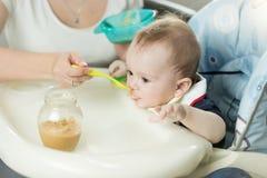Close-up van 9 van de babymaanden oud jongen die fruitsaus van glas j eten Royalty-vrije Stock Foto