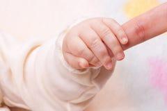 Close-up van van de de handholding van de baby de vinger van de moeder Royalty-vrije Stock Afbeeldingen
