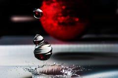 Close-up van van de water dalende dalingen en plons kroon van rood Kerstmisspeelgoed Royalty-vrije Stock Foto's