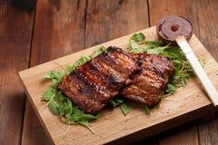 Close-up van varkensvleesribben met BBQ saus worden geroosterd en gekarameliseerd in honing op een bed van arugula die Smakelijke Stock Afbeeldingen