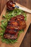 Close-up van varkensvleesribben met BBQ saus worden geroosterd en gekarameliseerd in honing op een bed van arugula die Smakelijke Stock Foto