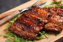 Close-up van varkensvleesribben met BBQ saus worden geroosterd en gekarameliseerd in honing op een bed van arugula die Smakelijke Royalty-vrije Stock Afbeeldingen