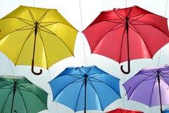 Close-up van veelvoudige gekleurde paraplu's die op draad hangen Stock Afbeeldingen