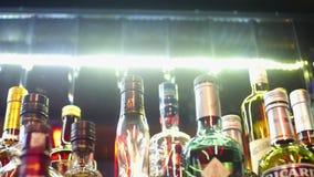 Close-up van verscheidenheid van alcohol in bar Kader De kleurrijke tribune van glasflessen op barteller op achtergrond van helde stock videobeelden