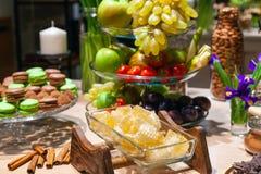 Close-up van verse die honingraten in kubussen in transparante vierkante glaskom bij buffet worden gesneden, pijpjes kaneel, vruc stock foto