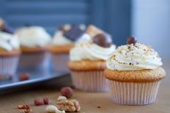 Close-up van verse smakelijke cupcakes met boterroom en poeder op een lichte houten oppervlakte royalty-vrije stock foto