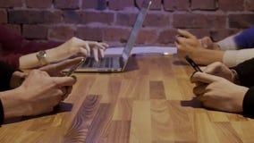 Close-up van vier mensen bij de lijst met een telefoon en laptop stock videobeelden
