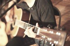 Close-up van vingers van het spelen akoestische gitaar Stock Foto