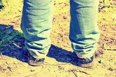 Close-up van voeten van een mens in oude jeans en oude schoenen gekleurd Royalty-vrije Stock Afbeelding