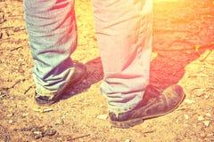 Close-up van voeten van een mens in oude jeans en uitgeputte schoenen T Royalty-vrije Stock Afbeelding