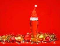 Close-up van volledig pilsener-glas bleek lagerbierbier of aal met Santa Claus of Kerstmis rode hoed wordt geschoten, de snuister royalty-vrije stock foto's
