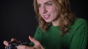 Close-up van volwassen Kaukasische vrouw het spelen videospelletjes op xbox met opwinding en hartstocht binnen stock video