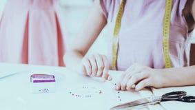 Close-up van vrouw bij het naaien van fabriek met kleurrijke spelden stock foto's
